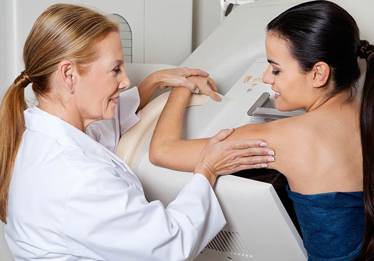Radiographer placing a patients body onto the mammography-pad-foam